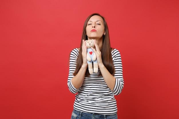 Portret oszałamiająca młoda kobieta w swobodnych ubraniach w paski, trzymająca w rękach pluszowego misia
