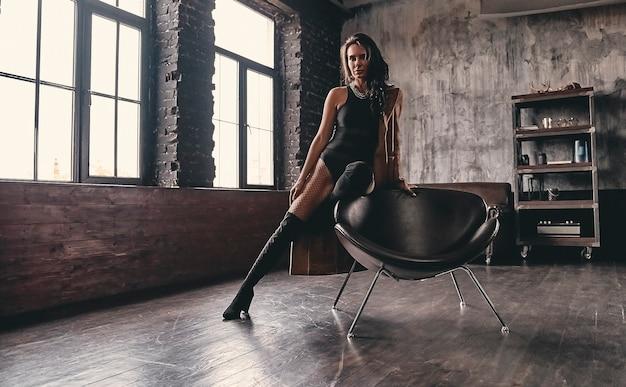 Portret oszałamiającej, pięknej brunetki z kręconymi włosami w czarnym jednoczęściowym kostiumie kąpielowym, w zamszowych wysokich butach i siateczkowych rajstopach, pozuje na fotelu odsłaniając długie, smukłe nogi.