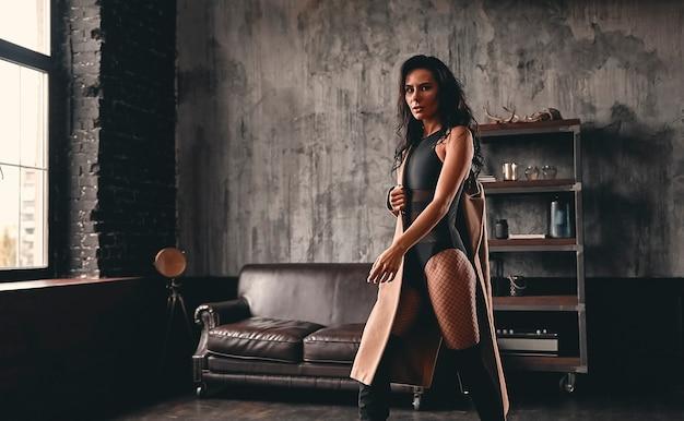 Portret oszałamiającej, pięknej brunetki z kręconymi włosami, w płaszczu i siateczkowych rajstopach, w wysokich czarnych butach, pozująca w ruchu.