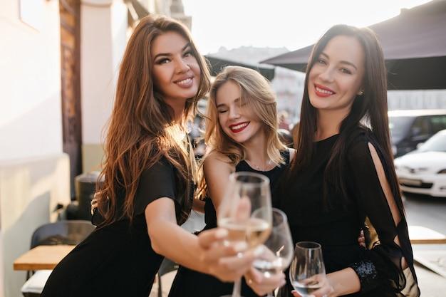 Portret oszałamiających pań spędzających weekend z kieliszkami pełnymi szampana na pierwszym planie