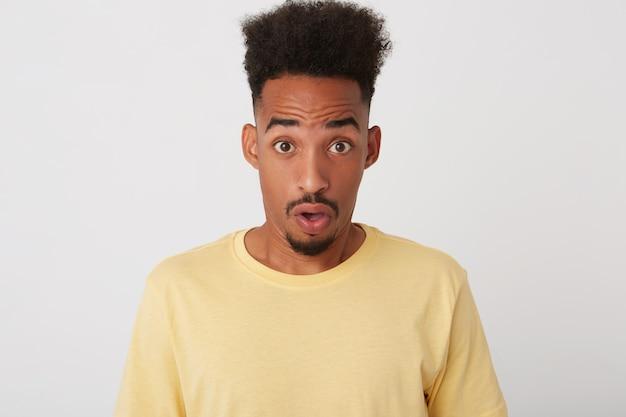 Portret oszołomionego, atrakcyjnego, ciemnoskórego, kręconego, nieogolonego faceta ze zdumieniem zaokrąglającym jego brązowe oczy