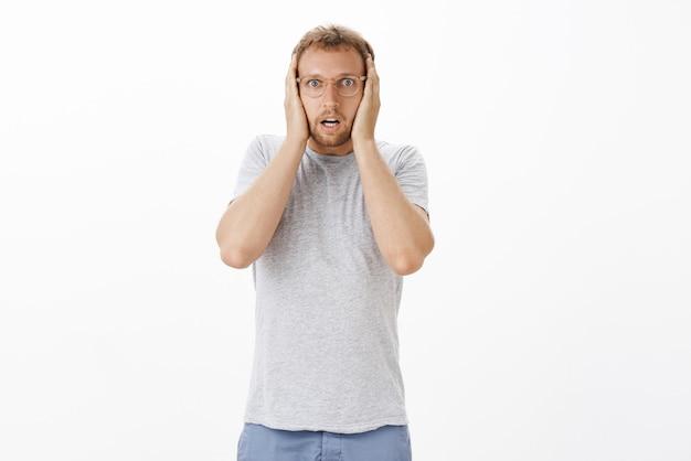 Portret oszołomionego i zszokowanego, intensywnego dorosłego mężczyzny w okularach trzymającego ręce na głowie, dyszącego i otwierającego usta od szoku, popełniającego straszny błąd, wywołując panikę nad białą ścianą