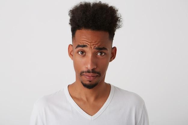 Portret oszołomionego młodego, całkiem nieogolonego mężczyzny z ciemną skórą marszczącą czoło