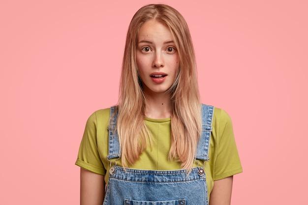 Portret oszołomionej blondynki ma zszokowany wyraz twarzy, zdumiony czymś nieoczekiwanym, ubrana w swobodny strój