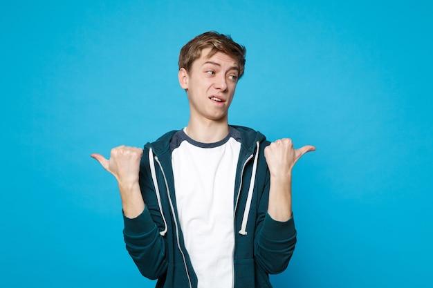 Portret oszołomiony pewny siebie młody człowiek stojący w ubraniu, wskazując kciuki na bok na białym tle na niebieskiej ścianie. ludzie szczere emocje, koncepcja stylu życia.