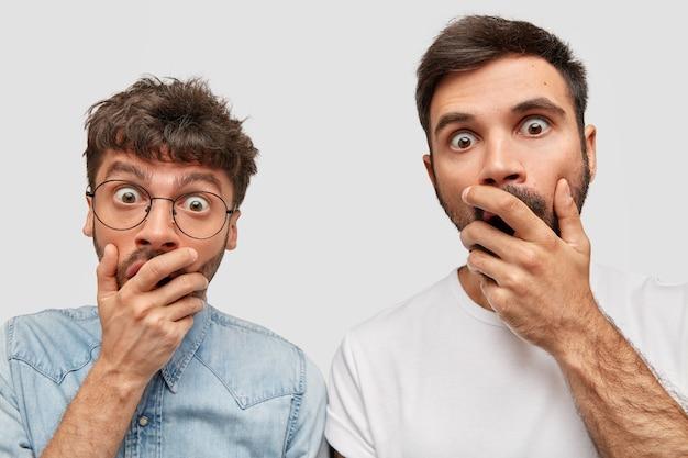 Portret oszołomionych dwóch brodatych mężczyzn z zamkniętymi ustami i dłońmi, wpatrujących się w nieoczekiwany wyraz twarzy, wyrażających strach i niedowierzanie, odizolowanych na białej ścianie. wspaniali bracia pozują w pomieszczeniach