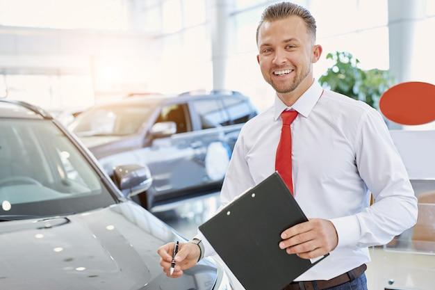 Portret otwartego, profesjonalnego sprzedawcy w salonie samochodowym