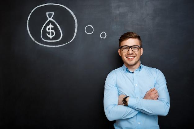 Portret pamiętający krzyżować ręki nad blackboard pieniądze pojęciem