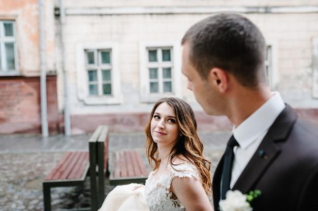 Portret pana młodego i panny młodej w pobliżu starego budynku, starego domu na zewnątrz, na zewnątrz. nowożeńcy spacerują ulicami lwowa.