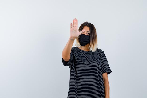 Portret pani pokazująca gest stopu w czarnej sukience, masce medycznej i patrząc zdecydowany widok z przodu