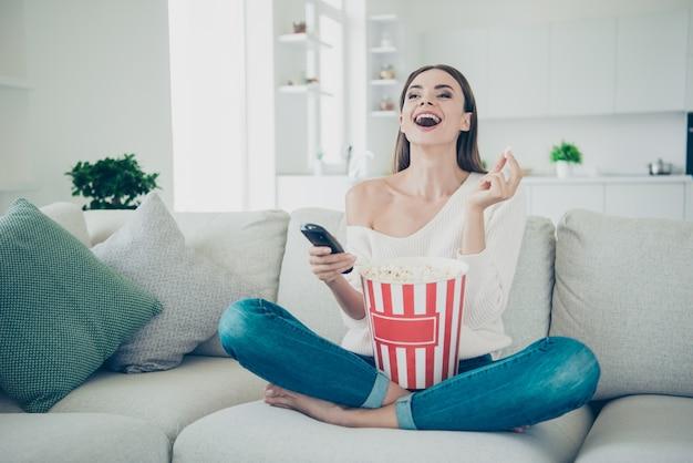 Portret pani śmiejąca się trzymać pilota popcorn
