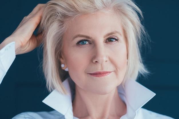 Portret pani w wieku. stylowa starsza blondynka z heterochromią.