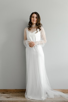 Portret panny młodej w białej i lekkiej sukni ślubnej na stylowym mundurze