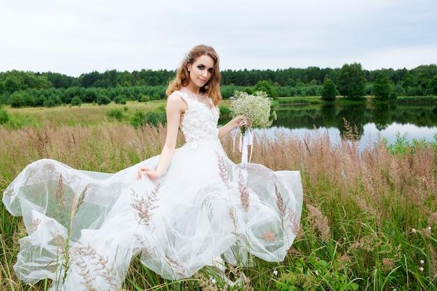Portret panny młodej w białej sukni ślubnej z bukietem w pobliżu jeziora