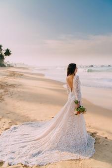 Portret panny młodej w pełnym wzroście na tropikalnej plaży