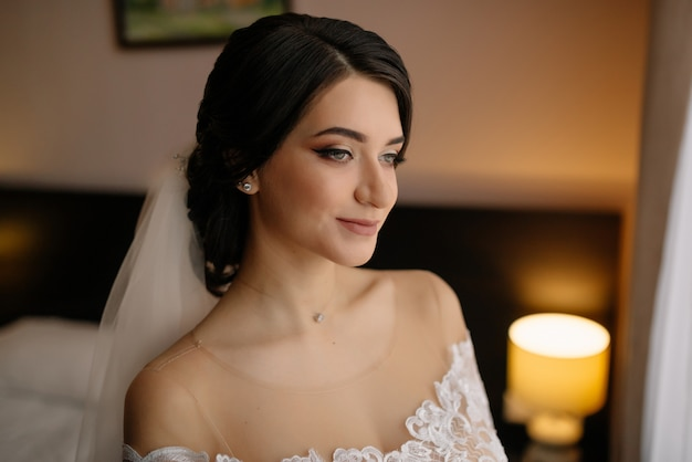 Portret panny młodej w poranek ślubu. pięknej narzeczonej z uśmiechem makijaż i fryzura.