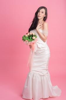 Portret panny młodej w sukni ślubnej na różowo.