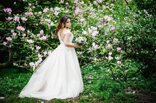 Portret panny młodej z bukietem ślubnym stojąc tyłem, na tle natura fioletowe, różowe kwiaty magnolii i zieleni. na dworze. patrząc w dół. pełna długość.