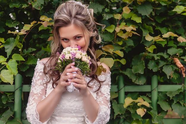 Portret panny młodej z bukietem ślubnym w ręce nad zielonymi liśćmi w parku. ładna kobieta w sukniach ślubnych w słoneczny dzień ślubu