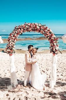Portret państwo młodzi pozuje blisko ślubnego tropikalnego łuku na plaży za niebieskim niebem i morzem. para młoda