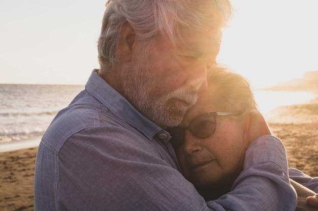 Portret para dwóch szczęśliwych seniorów i dojrzałych i starych ludzi na plaży razem. emeryt i emeryt pociesza smutną przygnębioną żonę płaczącą.
