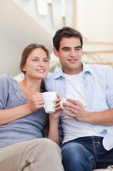 Portret para pije kawę podczas gdy oglądający tv