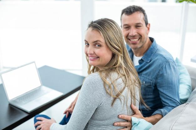 Portret para siedzi na kanapie i za pomocą laptopa w salonie