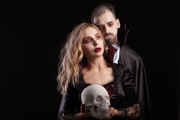 Portret para wampirów pozuje na halloween na czarnym tle. przystojny mężczyzna w stroju drakuli. uwodzicielska wampirzyca.
