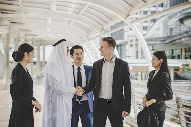 Portret partnerzy biznesowi wita each inny handshaking w drodze do biura.