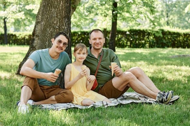 Portret pary gejów siedzącej na trawie z dzieckiem i wspólnie jedzących lody