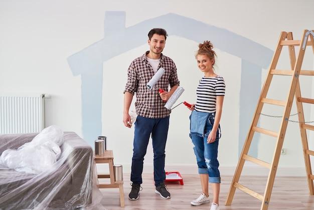 Portret pary malującej ścianę wewnętrzną w nowym mieszkaniu