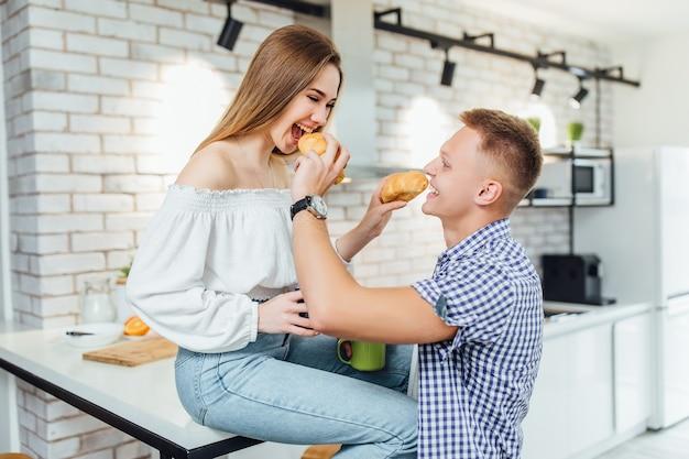 Portret pary przytulanie w kuchni i opierając się na kuchennym blacie z rogalikiem.