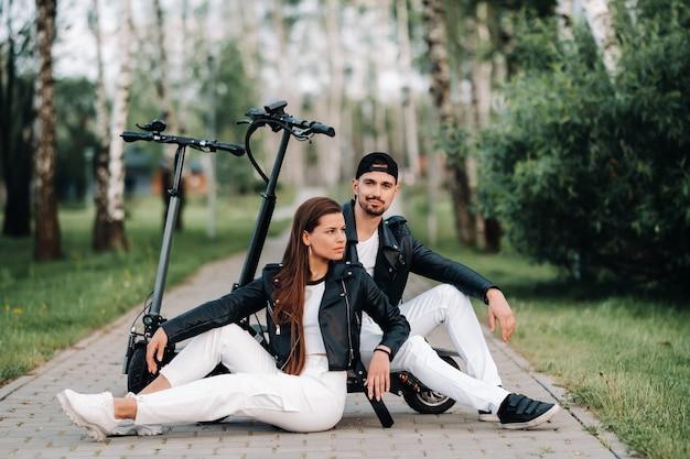 Portret pary siedzącej w pobliżu hulajnóg elektrycznych, ciesząc się razem czas na łonie natury, dwoje kochanków na skuterach elektrycznych. ludzie na skuterach.
