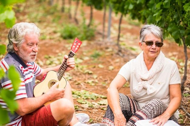 Portret pary starszych starszych dorosłych dorosłych przebywających razem na wsi, ciesząc się wypoczynkową aktywnością muzyczną