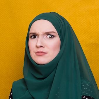 Portret patrzeje kamerę przeciw żółtemu tłu zmieszana kobieta