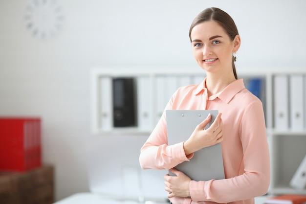 Portret patrzeje kamerę trzyma falcówkę w jej rękach i ono uśmiecha się biznesowa kobieta