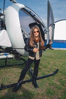 Portret pełnej długości animowanej dziewczyny w okularach przeciwsłonecznych w pobliżu otwartego helikoptera