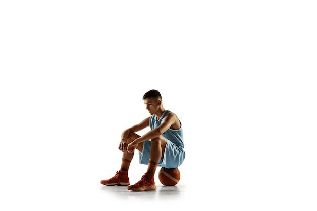 Portret pełnej długości młody koszykarz z piłką na białym tle na tle białego studia. nastolatek pewnie pozuje z piłką. pojęcie sportu, ruchu, zdrowego stylu życia, reklamy, akcji, ruchu.