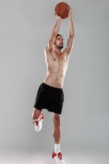 Portret pełnej długości skoncentrowanego młodego mężczyzny bez koszuli