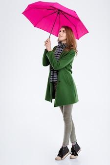 Portret pełnej długości uśmiechniętej kobiety stojącej z różowym parasolem i patrzącej w górę na białym tle