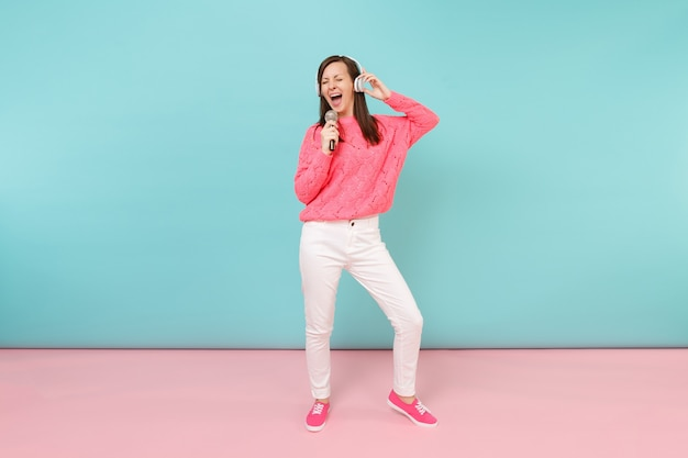 Portret pełnej długości zabawnej kobiety w swetrze z dzianiny, białych spodniach, słuchawkach śpiewających piosenkę w mikrofonie
