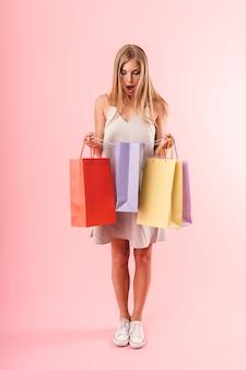 Portret pełnej długości zdziwionej młodej kobiety w sukience wyrażającej zaskoczenie i trzymającej kolorowe papierowe torby na zakupy odizolowane na różowej ścianie