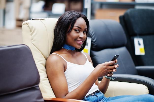 Portret perfect amerykanin afrykańskiego pochodzenia kobieta używa jej smartphone w sklepie.