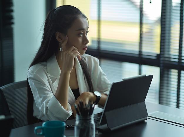Portret pewna bizneswoman pracuje swoją strategię, patrząc na okna