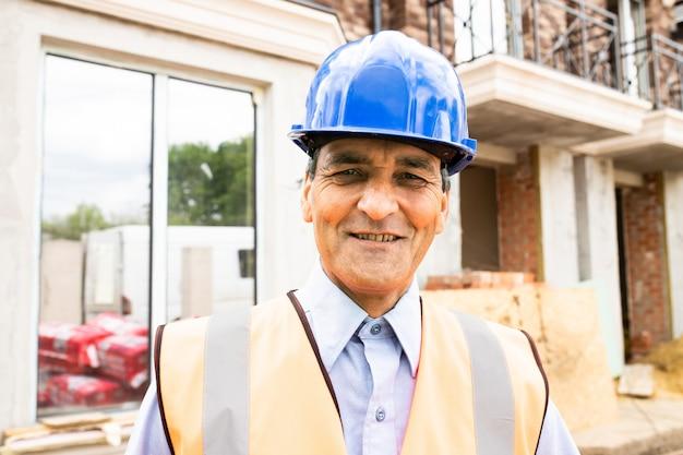 Portret pewnego indyjskiego męskiego pracownika budowlanego na budowie pewny siebie kierownik budowy ubrany w kask i zachodni udany dojrzały inżynier budownictwa na budowie