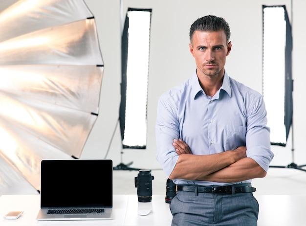 Portret pewnego siebie biznesmena stojącego z założonymi rękoma w studio