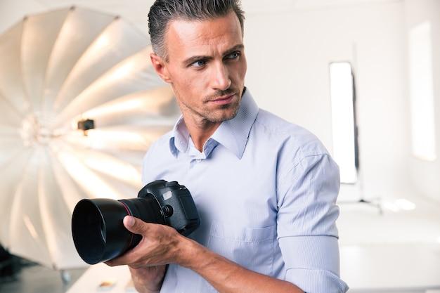 Portret pewnego siebie fotografa trzymającego aparat i odwracającego wzrok w studio