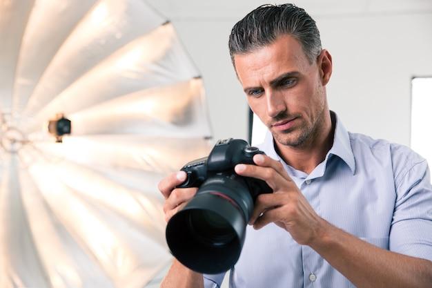 Portret pewnego siebie fotografa używającego aparatu w studio