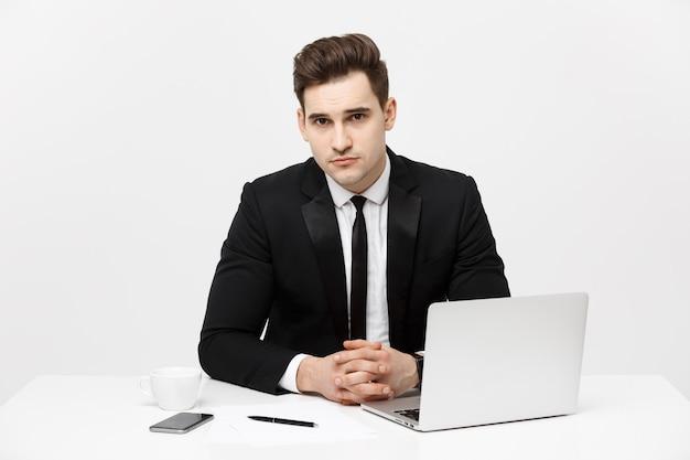 Portret pewnego siebie menedżera siedzącego przy biurku i patrzącego na kamerę portret biznesmena pracującego...