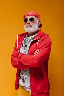 Portret pewnego siebie mężczyzny w czerwonej czapce i okularach przeciwsłonecznych